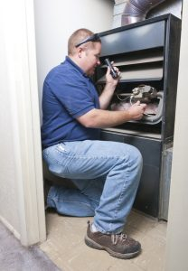 service professional working on the inside of a heating system