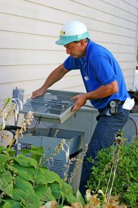 technician working on the outside unit of an air conditioner