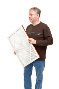 man holding air filter, imposed on white background